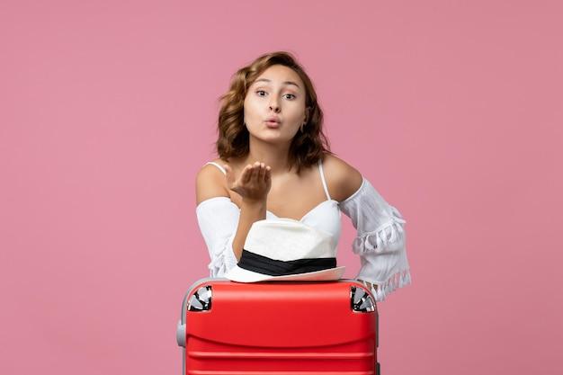 Vooraanzicht van jonge vrouw die zich voorbereidt op vakantie die luchtkussen op roze muur verzendt