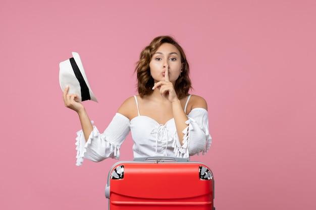 Vooraanzicht van jonge vrouw die zich voorbereidt op vakantie met rode tas die zich voordeed op de roze muur