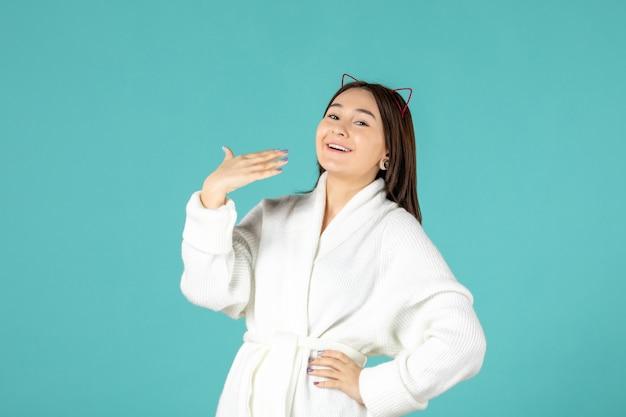 Vooraanzicht van jonge vrouw in badjas op blauwe muur