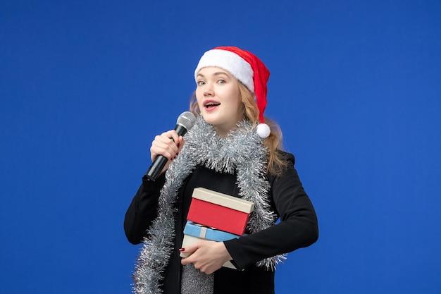 Vooraanzicht van jonge vrouw in karaokefeest met cadeautjes op blauwe muur