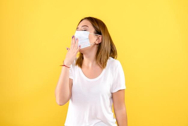 Vooraanzicht van jonge vrouw in masker op gele muur