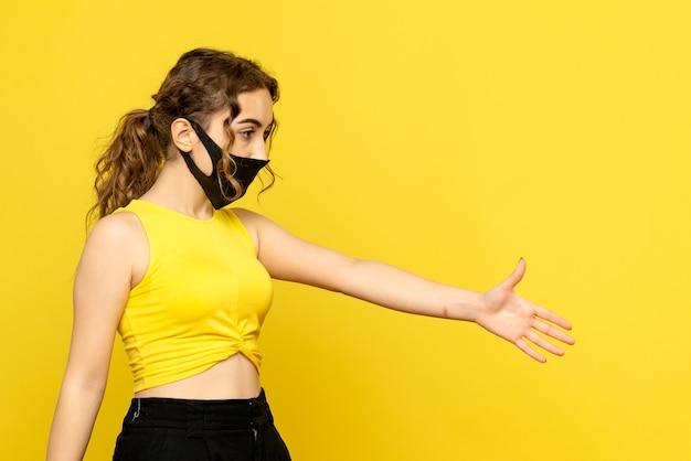 Vooraanzicht van jonge vrouw in maskergroet op gele muur