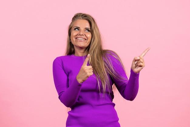 Vooraanzicht van jonge vrouw in mooie paarse jurk poseren met glimlach op roze muur