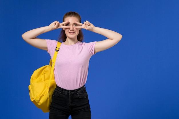 Vooraanzicht van jonge vrouw in roze t-shirt met gele rugzak, glimlachend op de lichtblauwe muur