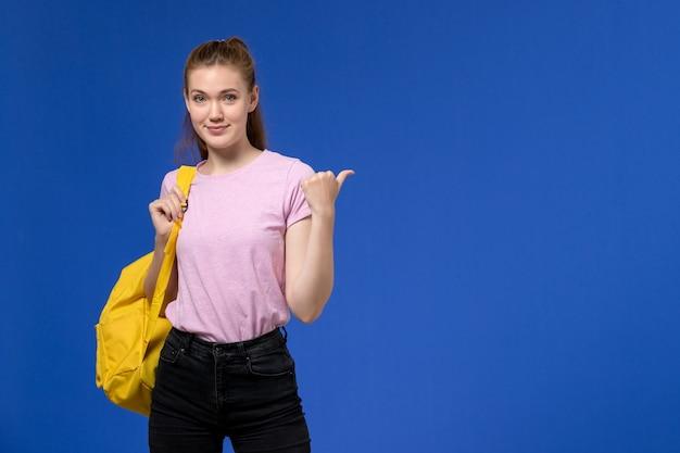 Vooraanzicht van jonge vrouw in roze t-shirt met gele rugzak poseren op de blauwe muur