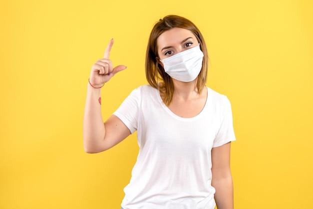 Vooraanzicht van jonge vrouw in steriel masker op gele muur