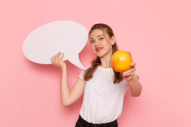 Vooraanzicht van jonge vrouw in wit t-shirt met grapefruit en wit bord glimlachend op roze muur