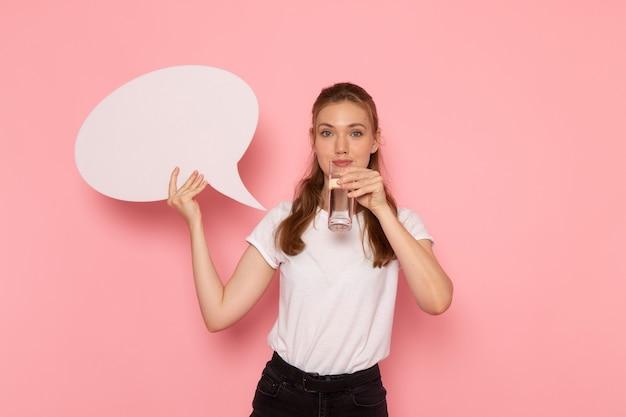 Vooraanzicht van jonge vrouw in wit t-shirt met wit bord en glas water op de roze muur