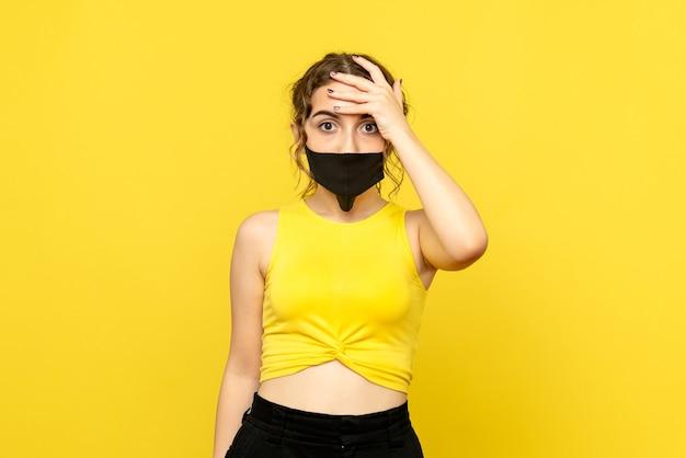 Vooraanzicht van jonge vrouw in zwart masker op een gele muur