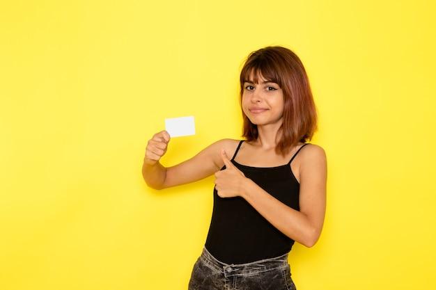 Vooraanzicht van jonge vrouw in zwart shirt en grijze spijkerbroek met witte kaart op gele muur