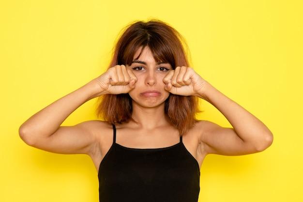 Vooraanzicht van jonge vrouw in zwart shirt en grijze spijkerbroek nep huilen op gele muur