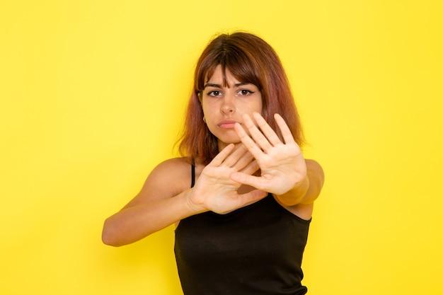 Vooraanzicht van jonge vrouw in zwart shirt en grijze spijkerbroek voorzichtig op gele muur