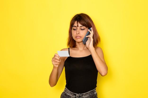 Vooraanzicht van jonge vrouw in zwart shirt met kaart en praten aan de telefoon op lichtgele muur