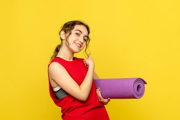 Vooraanzicht van jonge vrouw lachend met paars tapijt op gele muur