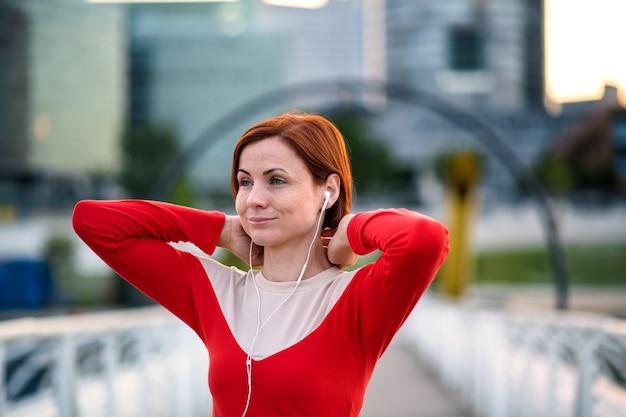 Vooraanzicht van jonge vrouw loper met koptelefoon in de stad, rustend op de brug.