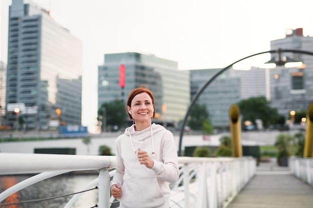 Vooraanzicht van jonge vrouw loper met koptelefoon joggen buiten in de stad.