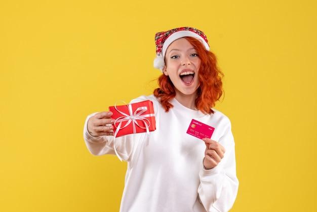 Vooraanzicht van jonge vrouw met aanwezige kerstmis en bankkaart op gele muur