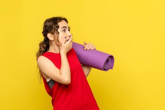 Vooraanzicht van jonge vrouw met bang gezicht op gele muur