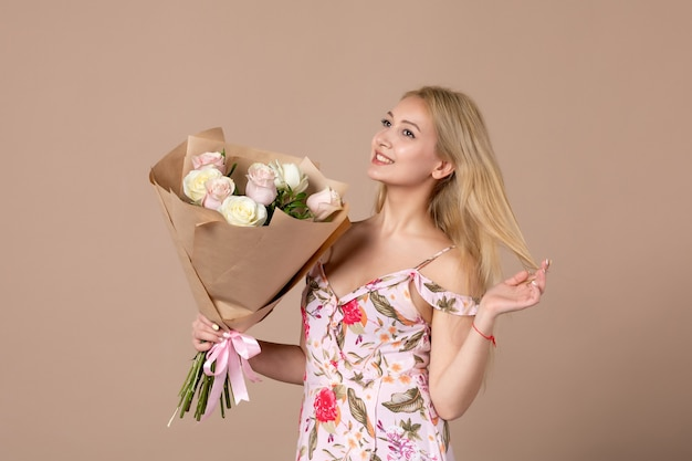 Vooraanzicht van jonge vrouw met boeket van mooie rozen op bruine muur