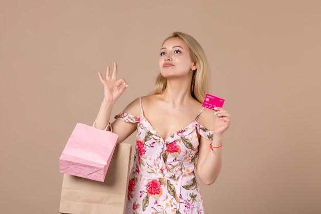 Vooraanzicht van jonge vrouw met boodschappentassen en bankkaart op bruine muur