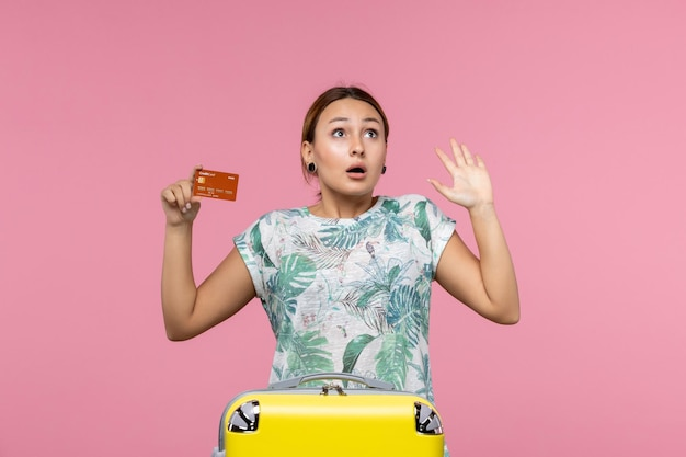 Vooraanzicht van jonge vrouw met bruine bankkaart op lichtroze muur light