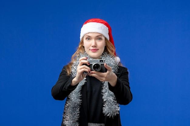 Vooraanzicht van jonge vrouw met camera op blauwe muur