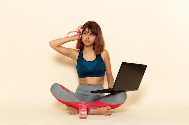 Vooraanzicht van jonge vrouw met fit lichaam in blauw shirt met behulp van laptop op de lichte witte muur