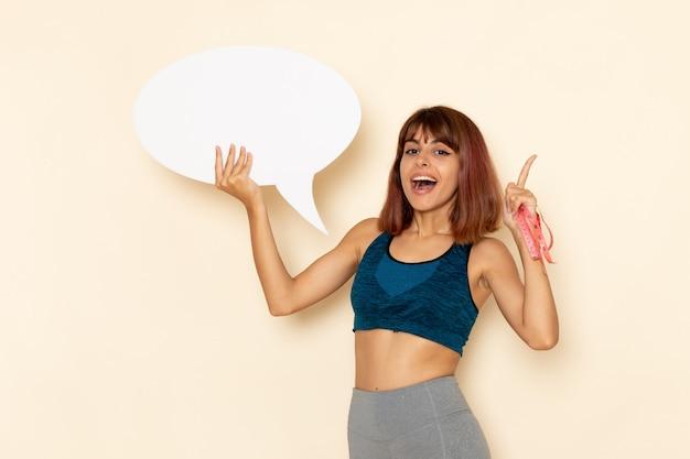 Vooraanzicht van jonge vrouw met fit lichaam in blauw shirt met groot wit bord op lichtwitte muur