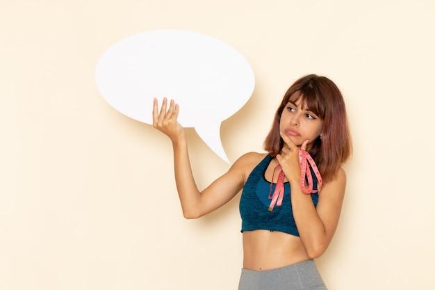 Vooraanzicht van jonge vrouw met fit lichaam in blauw shirt met wit bord op de lichte witte muur