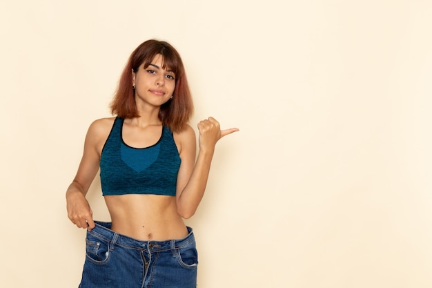 Vooraanzicht van jonge vrouw met fit lichaam in blauw shirt poseren op de lichte witte muur