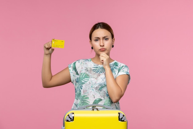 Vooraanzicht van jonge vrouw met gele bankkaart op de roze muur