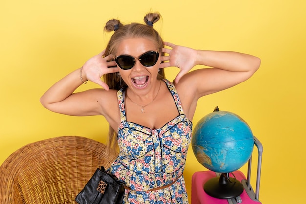 Vooraanzicht van jonge vrouw met globe en roze tas in zomervakantie poseren op een gele muur
