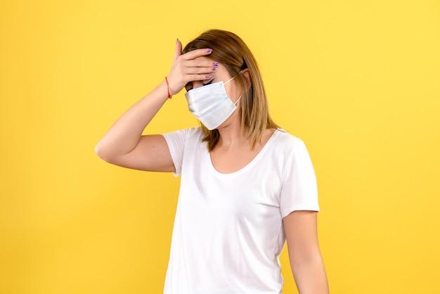 Vooraanzicht van jonge vrouw met hoofdpijn op gele muur
