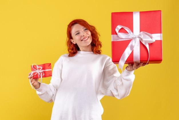 Vooraanzicht van jonge vrouw met kerstcadeautjes op gele muur