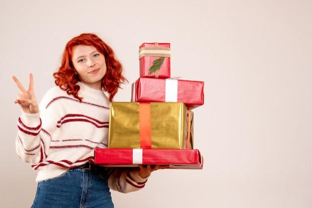 Vooraanzicht van jonge vrouw met kerstcadeautjes op witte muur