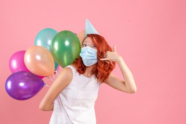 Vooraanzicht van jonge vrouw met kleurrijke ballonnen in steriel masker op de roze muur