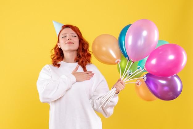 Vooraanzicht van jonge vrouw met kleurrijke ballonnen op de gele muur