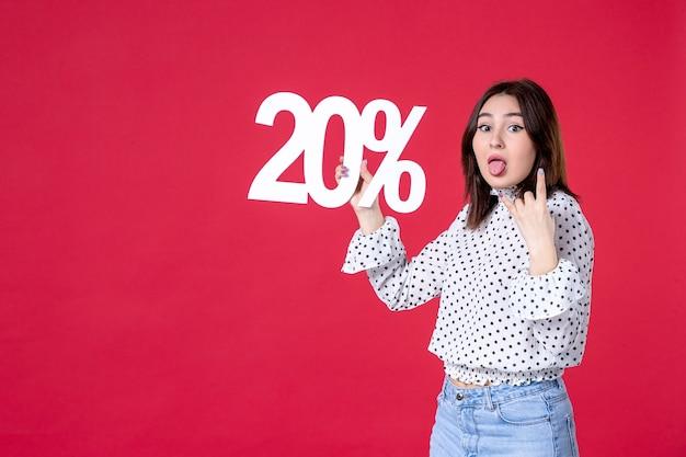 Vooraanzicht van jonge vrouw met korting op rode muur