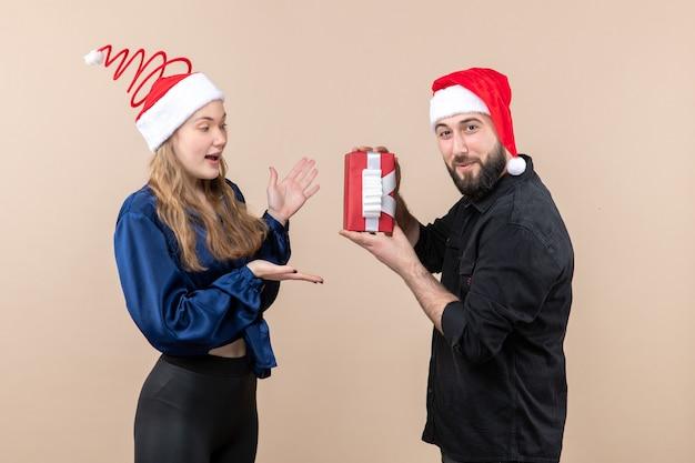 Vooraanzicht van jonge vrouw met man die haar een cadeautje geeft op de roze muur