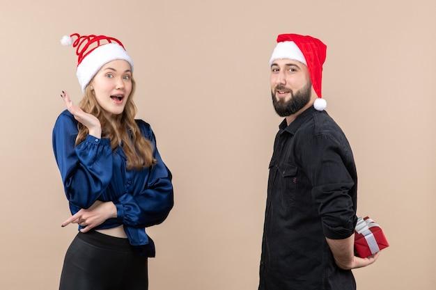 Vooraanzicht van jonge vrouw met man die zich voorbereidt om haar een cadeautje te geven op de roze muur