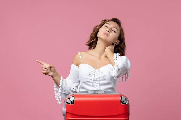Vooraanzicht van jonge vrouw met nekpijn met rode vakantietas op roze muur