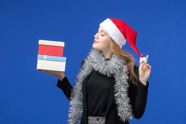 Vooraanzicht van jonge vrouw met nieuwjaarscadeautjes op blauwe muur