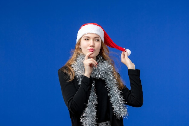 Vooraanzicht van jonge vrouw met nieuwjaarsslingers op blauwe muur