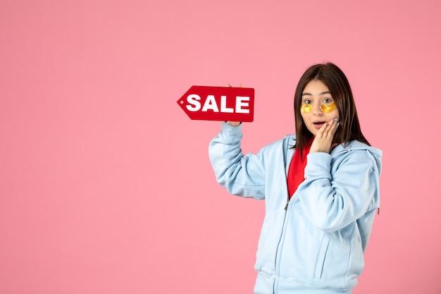 Vooraanzicht van jonge vrouw met ooglapjes die rode verkoopbanner op roze muur houden
