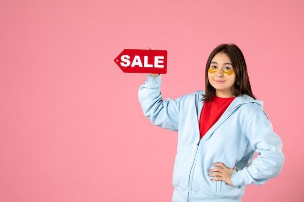 Vooraanzicht van jonge vrouw met ooglapjes die verkoopbanner op roze muur houden