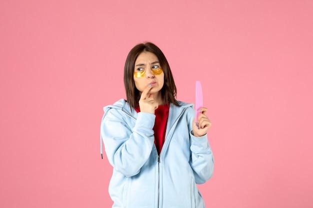 Vooraanzicht van jonge vrouw met ooglapjes en nagelvijl op roze muur