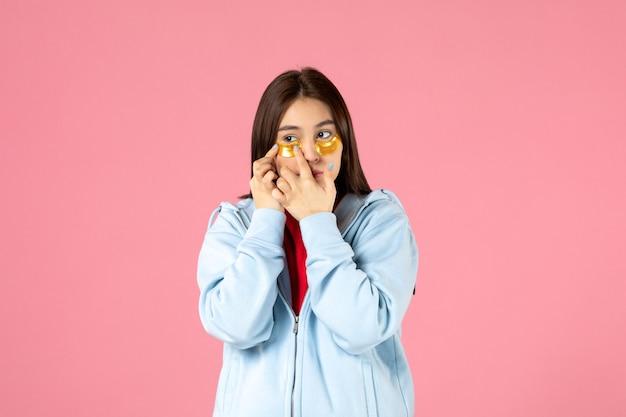 Vooraanzicht van jonge vrouw met ooglapjes onder haar ogen op roze muur