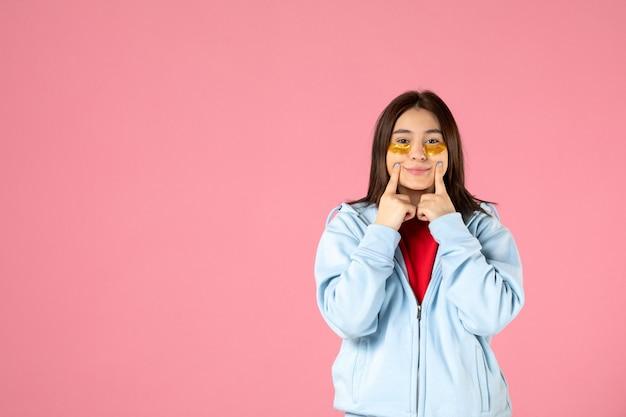 Vooraanzicht van jonge vrouw met ooglapjes op roze muur