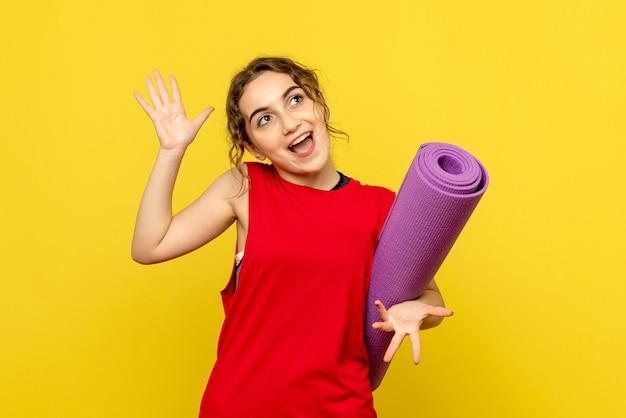 Vooraanzicht van jonge vrouw met paars tapijt op een gele muur