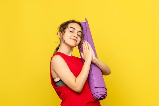 Vooraanzicht van jonge vrouw met paars tapijt op gele muur